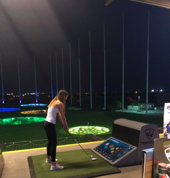 Demie golfing at Top Golf